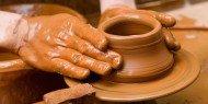 Potter's hands working clay pot